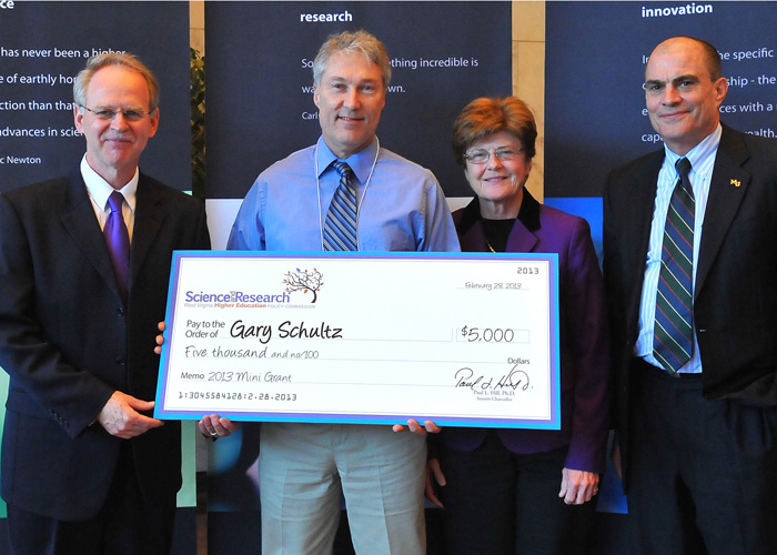 Photo of Dr. Gary Schultz receiving a giant check representing his grant award